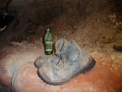 Old mining boots and bottle to hold his candle